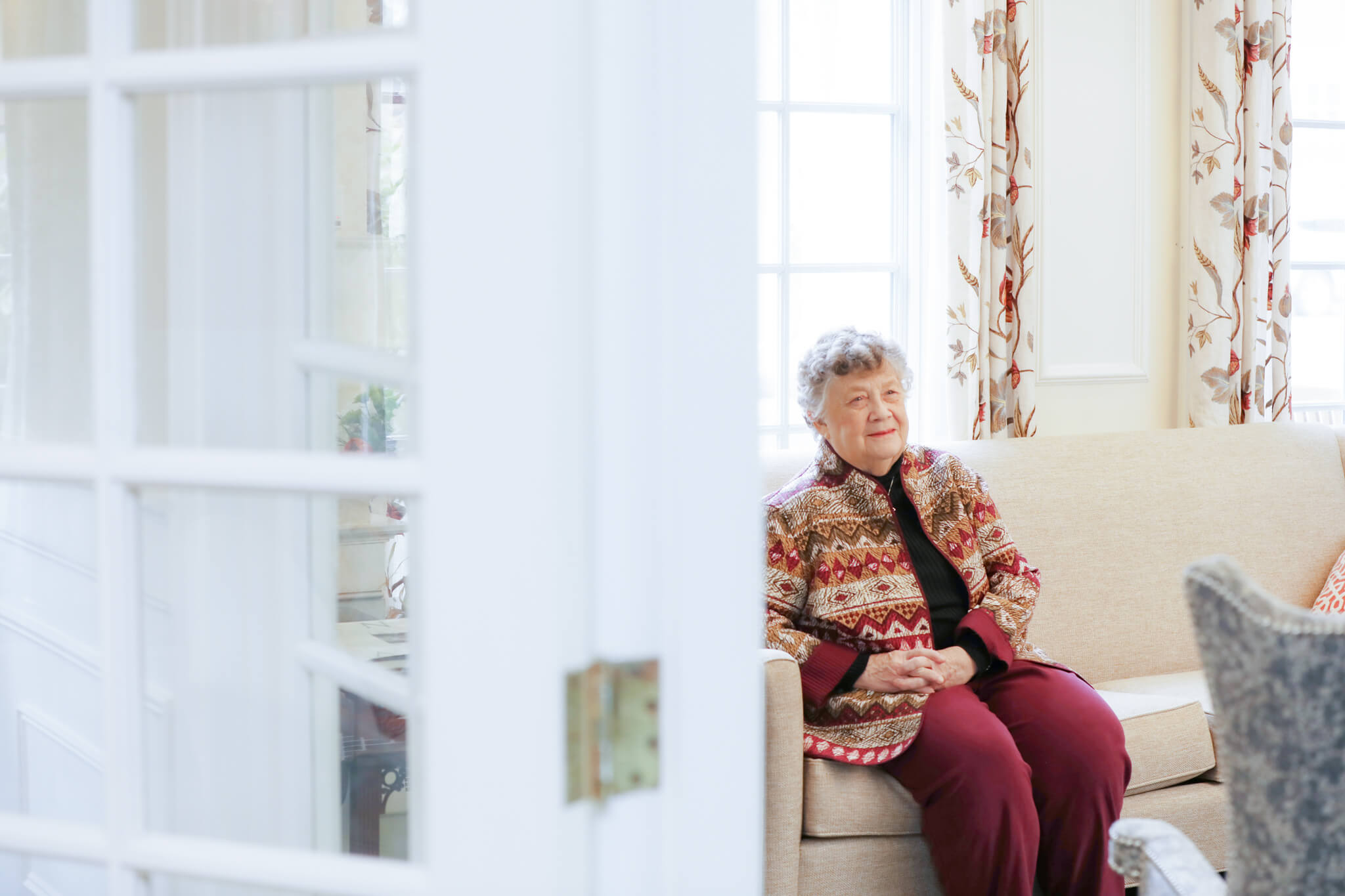 Lilian Warner Sitting on Couch in a Sunny Room